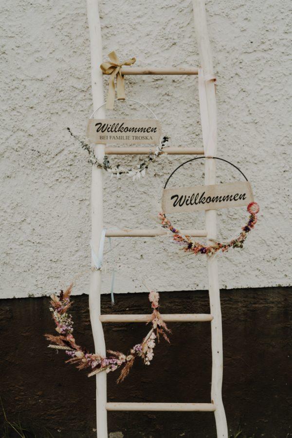 Blumenkranz an Leiter befestigt